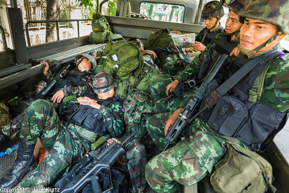 """20 MAY 2104 - BANGKOK, THAILAND: Thai soldiers sleep in the back of a truck on Ratchadamri Road in Bangkok after the army put soldiers on the street following the declaration of martial law. The Thai Army declared martial law throughout Thailand in response to growing political tensions between anti-government protests led by Suthep Thaugsuban and pro-government protests led by the """"Red Shirts"""" who support ousted Prime Minister Yingluck Shinawatra. Despite the declaration of martial law, daily life went on in Bangkok in a normal fashion. There were small isolated protests against martial law, which some Thais called a coup, but there was no violence.   PHOTO BY JACK KURTZ"""