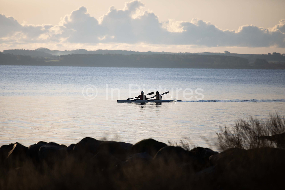 Two people in a double kayak pass by in the morning sun, Oct 29th 2019, Skæring, Århus, Denmark. The bay is much used by kayaks, rowers and small sailing boats with Kalø Vig Marina nearby. It is autumn and the sailing and rowing season is nearly over. The beach is nearly deserted and is between Århus and the neaby coal power plant Studstrup.