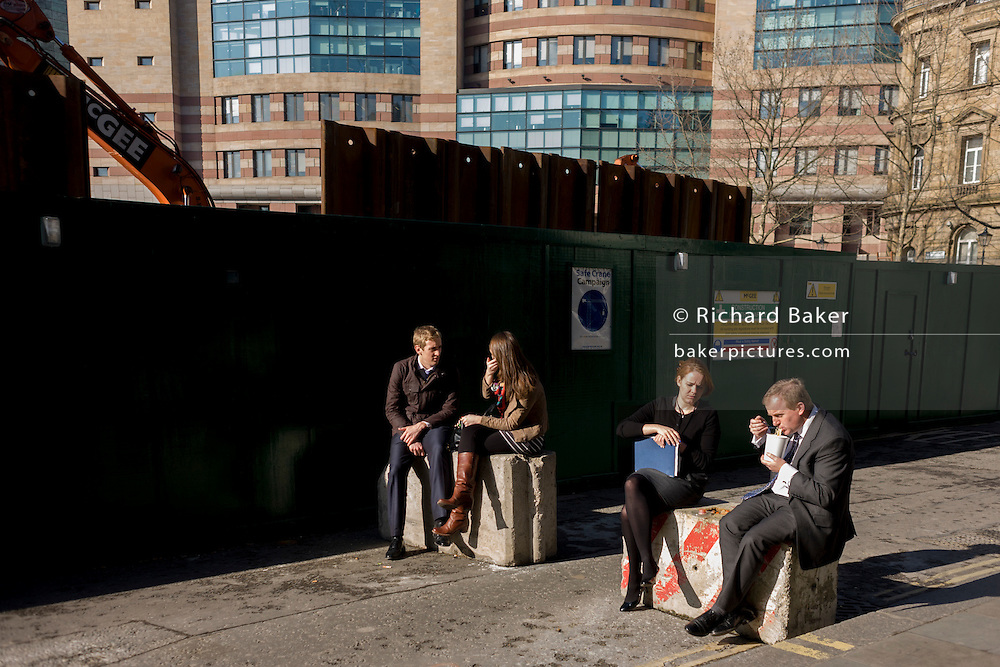 Lunchtime office workers enjoy lunchtime in spring sunshine sitting on concrete barriers and surrounded by office buildings.