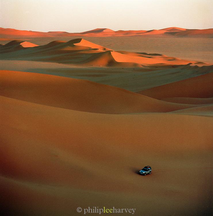 4x4 vehicle driving across dunes at sunset, Sahara Desert, Libya