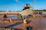 Two miners work alongside the bed of the Madre de Dios River in the extraction of gold by suction using a gasoline engine in the Peruvian Amazon. Boca Colorado, Peru.