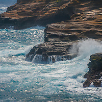 Pacific Ocean waves crash onto eroded sandstone cliffs on the southeast shore of Oahu, Hawaii.