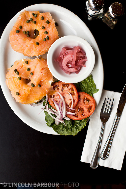 Overhead shot of bagel and lox breakfast on a black table