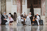 Damasucs, Syria - June 3, 2010: Mothers and kids sit in the courtyard of the Umayyad Mosque. Also called the Great Mosque, it was built on the site of a Christian basilica in the 8th century.