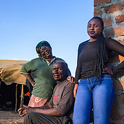 INDIVIDUAL(S) PHOTOGRAPHED: From left to right: Theresa Nguluwe, Brasford Nguluwe and Ruth Kampangele. LOCATION: Kuku Compound, Chitukuko, Chilanga District, Lusaka, Zambia. CAPTION: Theresa Nguluwe (left), Brasford Nguluwe (centre) and Ruth Kampangele (right) in Chitukuko, Lusaka. Ruth built her grandparents a house after attending a training programme and qualifying as a bricklayer during the building of the Chitukuko Community School in 2016 as part of Build It International's Training into Work & Community Building programme. Build It International is a charity that trains unemployed young people in Zambia to become builders, while at the same time building vital schools and clinics in communities with little or nothing by way of resources.
