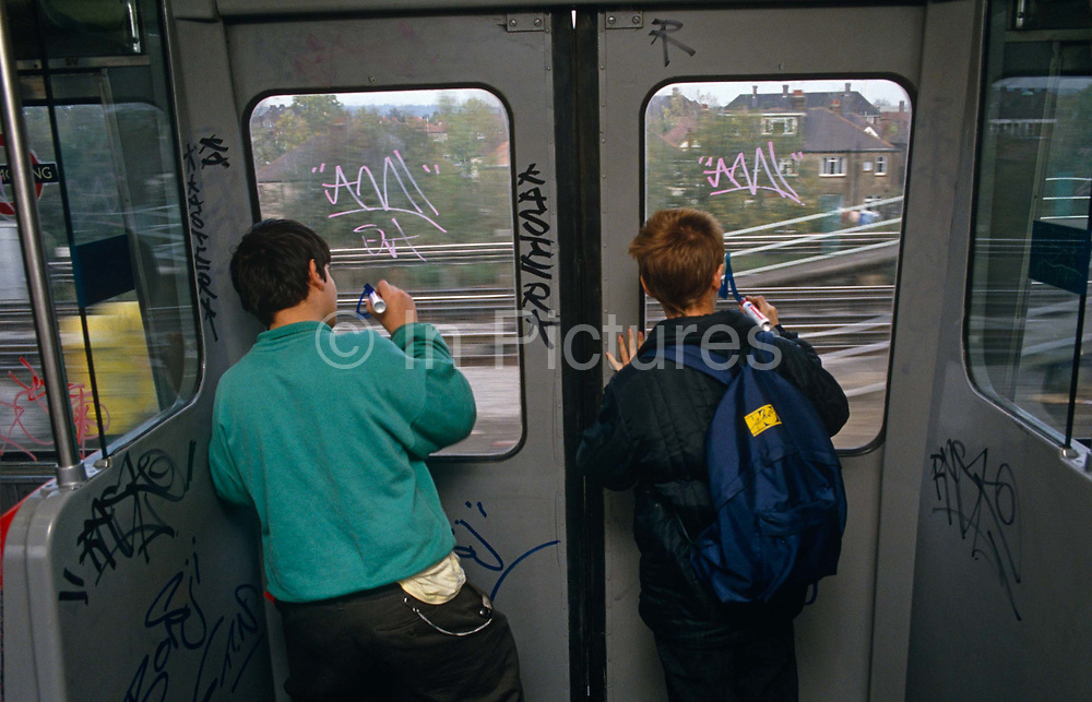 Seen from behind, two young boys are busy writing their graffiti tags on windows on a London underground tube train, during an overland section of the capital's rail system near Ladbroke Grove. Armed with heavy-duty semi-permanent marker pens, they lads are committing the crime of defacement and criminal damage to London Underground property, a persistent problem that costs the transport company network up to £3 million a year to remove. Partitions and glass are being scribbled on with their unique identity signatures used by kids of this age to leave as a mark of their presence, like animals instinctively leave a scent on a street corner. If caught, juvenile delinquents like these may escape with only a caution because of their age but older ones are prosecuted, though some times after leaving many thousands of tags across their neighbourhood.