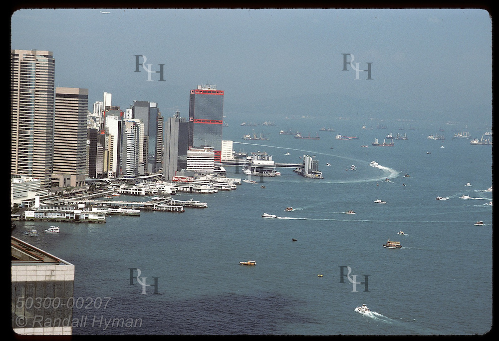 Harbor teems w/ freighters off north point of Central District in mid-day view aerial view. Hong Kong