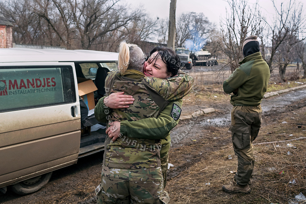 Julia Paevska is embracing soldier Jana Chervonaya, during a visit to a small military base named 'zamok', Ukrainian for 'castle', in Luhanske, between Ukraine-controlled Bakhmut and separatist-controlled areas of Debaltseve.