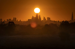 © Licensed to London News Pictures. 07/05/2021. London, UK. The morning sun rises over the City of London appearing to touch the top of 22 Bishopsgate tower. Colder wetter weather is expected over the weekend and into next week. Photo credit: Peter Macdiarmid/LNP