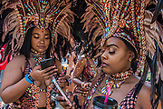 Dancers relax with social media as they prepare for the parade - The Monday of the Notting Hill Carnival. The annual event on the streets of the Royal Borough of Kensington and Chelsea, over the August bank holiday weekend. It is led by members of the British West Indian community, and attracts around one million people annually, making it one of the world's largest street festivals.
