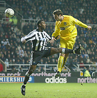 Photo. Andrew Unwin.<br /> Newcastle United v Leeds United, Barclaycard Premier League, St James Park, Newcastle upon Tyne 07/01/2004.<br /> Leeds' Mark Viduka (r) beats Newcastle's Titus Bramble (l) in the air but is unable to get his header past Shay Given.