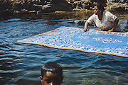 A nubian woman cleaning carpets in the Nile at Kodi, Seheil Island, Aswan, Egypt 2014