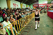 Male wrestler making his entrance and signalling to crowd. Lucha Libre wrestling origniated in Mexico, but is popular in other latin Amercian countries, including in La Paz / El Alto, Bolivia. Male and female fighters participate in the theatrical staged fights to an adoring crowd of locals and foreigners alike.