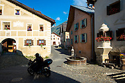 Motorcycling in the Engadine Valley, the village of Guarda with old painted stone 17th Century buildings, Switzerland