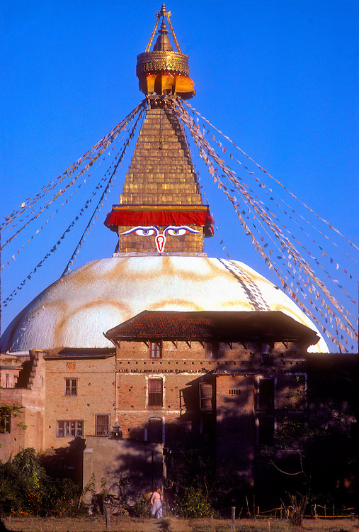 The eyes of the compassionate Lord Buddha watch over the Kathmandu Valley from this great stupa -- a kind of Buddhist shrine -- adorned with prayer flags and a tapering golden tower, while in the foreground a woman carrying a basket on her back strides into a field.