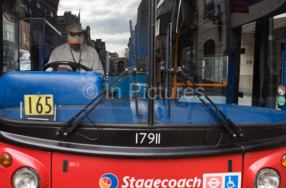 A driver with the bus company Stagecoach reads during a well-earned rest from busy London traffic. Seen from the front end of his red London bus, the man sits in the driver's cab looking down. Wearing a cap bearing the corporate logo of phone operator Vodafone, the man's attention is on his reading material while parked in Conduit Street, Westminster. We see the company name along with the Transport for London logo and a wheelchair access badge. The man may be half-way through his shift taking Londoners to various destinations in the capital.
