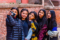 A group of teenage Nepalese girls taking a selfie in Durbar Square, Bhaktapur, Kathmandu Valley, Nepal.