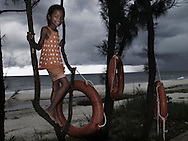 A little vietnamese girl poses along the beach, perched on a tree. Lifebuoys hangs on trunks. Phan Thiet, Vietnam, Asia.