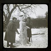 Magic lantern slide two boys making a snowman in a garden, England, UK c 1900-1910