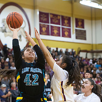 Navajo Prep Eagle Caylynn Lee (42) drives to the basket while Tohatchi Cougar Cameron Tsosie (20) defends at Tohatchi High School Thursday night in Tohatchi.