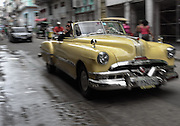 A  vintage car speeds down Centro Habana's busy Neptuno Street.
