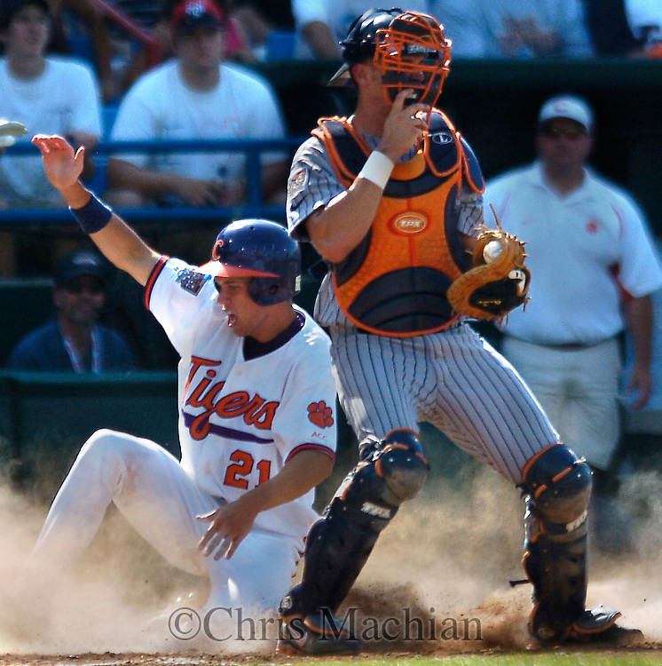 06/19/2006 Tyler Colvin slides in and scores the  third run for Clemson to tie it at three in the first inning as Cal State Fullerton's John Curtis watches during game nine of the College World Series in Omaha Nebraska Tuesday afternoon..(photo by Chris Machian/Prairie Pixel Group)