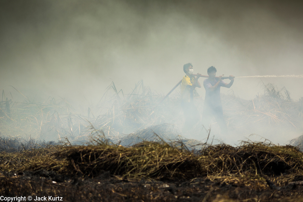 17 MARCH 2014 - PHRAEKSA, SAMUT PRAKAN, THAILAND:  Residents of a landfill try to put out a fire burning in the landfill. A fire apparently spontaneously started in the landfill in Samut Prakan over the weekend and threatens the homes of workers who live near the landfill. The fire Officials said the fire started when garbage in the landfill burst into flames and the flames were spread by hot, dry winds. Hundreds of people have been evacuated because of the fire and acrid smoke from the fire has spread as far as Bangkok. It hasn't rained in central Thailand in more than three months, impacting agriculture and domestic water use. Many farms are running short of irrigration water and salt water from the Gulf of Siam has come up the Chao Phraya River and infiltrated the water plants in Pathum Thani province that serve Bangkok.   PHOTO BY JACK KURTZ