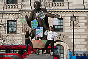 Inspired by Swedish teenager Greta Thunberg and organised by Youth Strike 4 Climate, British eco-aware school and college-age pupils protest about Climate Change on the statue of David Lloyd George in Parliament Square during their walkout from classes, on 15th February 2019, in Westminster, London England.