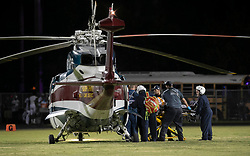 August 18, 2018 - Wellington, Florida, U.S. - A shooting victim is loaded into Trauma Hawk on the field at Palm Beach Central High School. Two adults were shot Friday night at a football game between Palm Beach Central and William T. Dwyer high schools, authorities said. The gunfire sent players and fans screaming and stampeding in panic during the fourth quarter of the game at Palm Beach Central High School in Wellington, Florida on August 17, 2018. (Credit Image: © Allen Eyestone/The Palm Beach Post via ZUMA Wire)