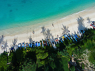 An aerial photograph of the late afternoon sun casting palm tree & boat mast shadows onto Lanikai Beach, Oahu, Hawaii