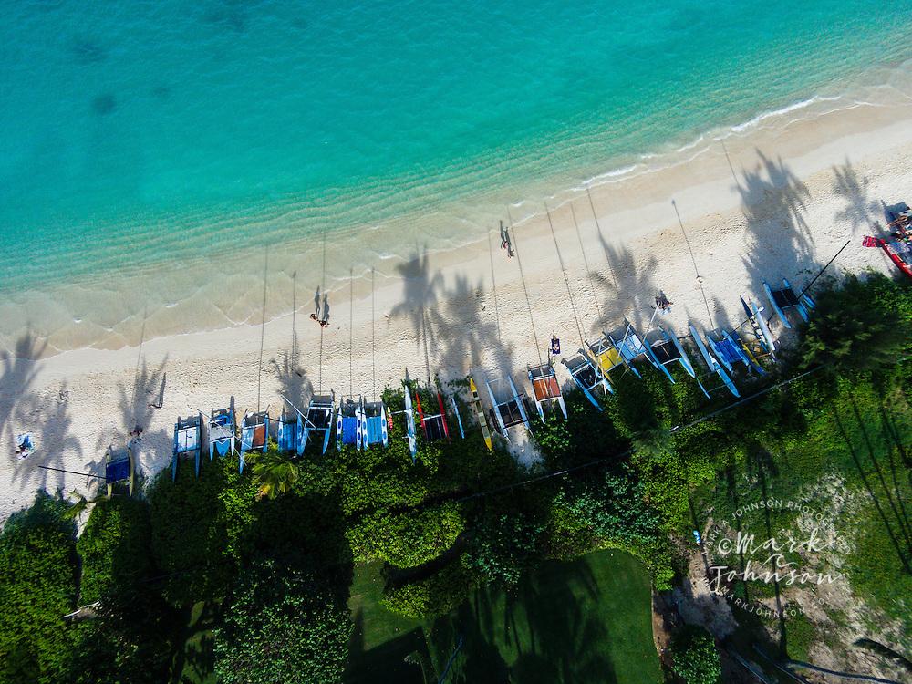 An aerial photograph of the late afternoon sun casting palm tree & boat mast shadows onto Lanikai Beach, Oahu, Hawaii