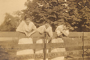 Three young girls hanging on a wooden fence.