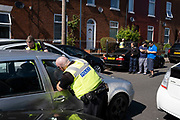 On John Street in the inner city area of Lozells, police chased a car up a dead end and arrested the driver after he had crashed into other cars parked in the street including a family who had been in one of the vehicles on 6th May 2020 in Birmingham, England, United Kingdom. Local people gathered on the street to watch the crime scene unfold. Coronavirus or Covid-19 is a new respiratory illness that has not previously been seen in humans. While much or Europe has been placed into lockdown, the UK government has put in place more stringent rules as part of their long term strategy, and in particular social distancing.