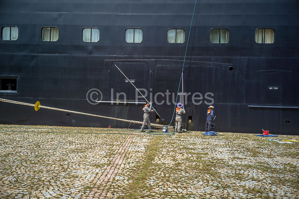 Crew paint and clean the hull of a cruise ship whilst passengers disembark in the port of Uturoa on the Island of Raiatea, French Polynesia.