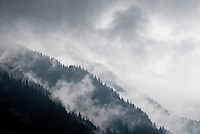 Storm clouds filter over forested ridgelines in the Chamonix Valley, France.