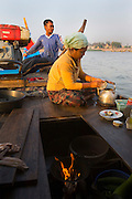 FISHERMEN MEKONG RIVER. South East Asia, Cambodia, Phnom Penh, Mekong River. The Cham fisher people live in various desolated villages along the banks of the Mekong and Tonle Sap rivers. The fisher families live like river gypsy nomads, working and living on their boats, sleeping under a sprung bamboo frame, all their worldly goods stored below deck. They live in extended families, with numerous boats, together for safety. Their diet is rice, vegetables and fish. Their sleek wooden boats are powered by petrol outboard motors with batteries or generators to supply lighting at night. Their fishing technique is laying nets twice or three times per day, which are weighted well below the surface, using old paint aerosal canisters as buoyant floaters, hanging just beneath the surface. These particular fisher families, living at the junction of the Mekong and Tonle Sap rivers, overlooked by Phnom Penh, sell their catch at the Vietnamese market, on the banks of the river. Their life and fortunes are controlled by the cycle of the river. As the river levels drop, so the quantity of fish decreases, until after the heavy floods of the monsoon they fill the river again. They are poor traditional Muslims, marginalised from mainstream society, living a third world life in the immmediate shadow of the first world. The Cham, originally a people of an ancient kingdom called Champa, are a small and disenfranchised community who were disinherited of their land. They are a socially important ethnic group in Cambodia, numbering close to 300,000. The Cham people, live in some 400 villages across Kampong Chnang and Kampong Cham provinces. Their religion is Muslim and their language belongs to the Malayo-Polynesian family. Their livelihoods are as diverse as rice farming, cattle trading, hunting and fishing.///Cham fisherman cook a midday meal. The pot is heated from below deck where a fire is burning.
