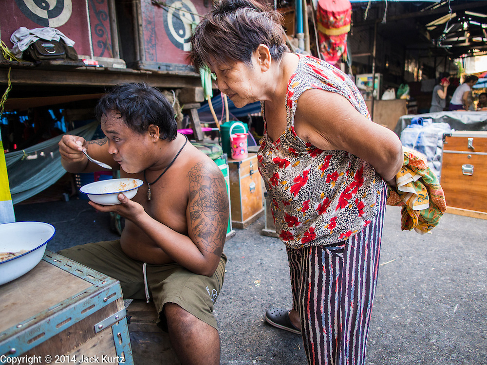 """18 AUGUST 2014 - BANGKOK, THAILAND: A member of the Lehigh Leng Kaitoung Opera troupe eats his dinner while another member of the troupe checks what he's having before a performance at Chaomae Thapthim Shrine, a small Chinese shrine in a working class neighborhood of Bangkok. The performance was for Ghost Month. Chinese opera was once very popular in Thailand, where it is called """"Ngiew."""" It is usually performed in the Teochew language. Millions of Chinese emigrated to Thailand (then Siam) in the 18th and 19th centuries and brought their culture with them. Recently the popularity of ngiew has faded as people turn to performances of opera on DVD or movies. There are still as many 30 Chinese opera troupes left in Bangkok and its environs. They are especially busy during Chinese New Year and Chinese holiday when they travel from Chinese temple to Chinese temple performing on stages they put up in streets near the temple, sometimes sleeping on hammocks they sling under their stage. Most of the Chinese operas from Bangkok travel to Malaysia for Ghost Month, leaving just a few to perform in Bangkok.     PHOTO BY JACK KURTZ"""