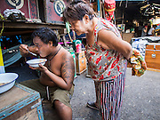 "18 AUGUST 2014 - BANGKOK, THAILAND: A member of the Lehigh Leng Kaitoung Opera troupe eats his dinner while another member of the troupe checks what he's having before a performance at Chaomae Thapthim Shrine, a small Chinese shrine in a working class neighborhood of Bangkok. The performance was for Ghost Month. Chinese opera was once very popular in Thailand, where it is called ""Ngiew."" It is usually performed in the Teochew language. Millions of Chinese emigrated to Thailand (then Siam) in the 18th and 19th centuries and brought their culture with them. Recently the popularity of ngiew has faded as people turn to performances of opera on DVD or movies. There are still as many 30 Chinese opera troupes left in Bangkok and its environs. They are especially busy during Chinese New Year and Chinese holiday when they travel from Chinese temple to Chinese temple performing on stages they put up in streets near the temple, sometimes sleeping on hammocks they sling under their stage. Most of the Chinese operas from Bangkok travel to Malaysia for Ghost Month, leaving just a few to perform in Bangkok.     PHOTO BY JACK KURTZ"