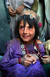 ZHARE DASHT,AFGHANISTAN - SEPT. 3: An Afghan Kuchi nomad girl who was living in camps around Spin Boldak, near the border of Pakistan and southern Afghanistan, relaxes after a grueling day of being relocated to the desolate, dusty encamptment of Zhare Dasht by the UNHCR September 3, 2002.  As an estimated 1.6 million Afghan refugees return to Afghanistan,  ethnic Pashtuns and Kuchi Nomads from northern Afghanistan are seeking safety in refugee camps in the south. Numbering up to 120,000,  they are fleeing the Tajik- and Uzbek-dominated cities of the north out of fear and prefer to live in a dismal camp  like Zhare Dasht which is set in the middle of a desert about 30 kilometers west of Kandahar. (Photo by Ami Vitale/Getty Images)