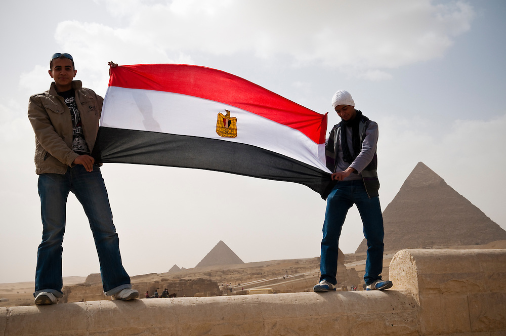 Two young men hold the Egyptian flag at the Pyramids in Giza, Egypt, nine days after the historic resignation of President Hosni Mubarak. (Cairo, Egypt - February 20, 2011)