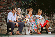 Four people read books and magazines on a park bench. A gray poodle sits with them. Collioure, France.