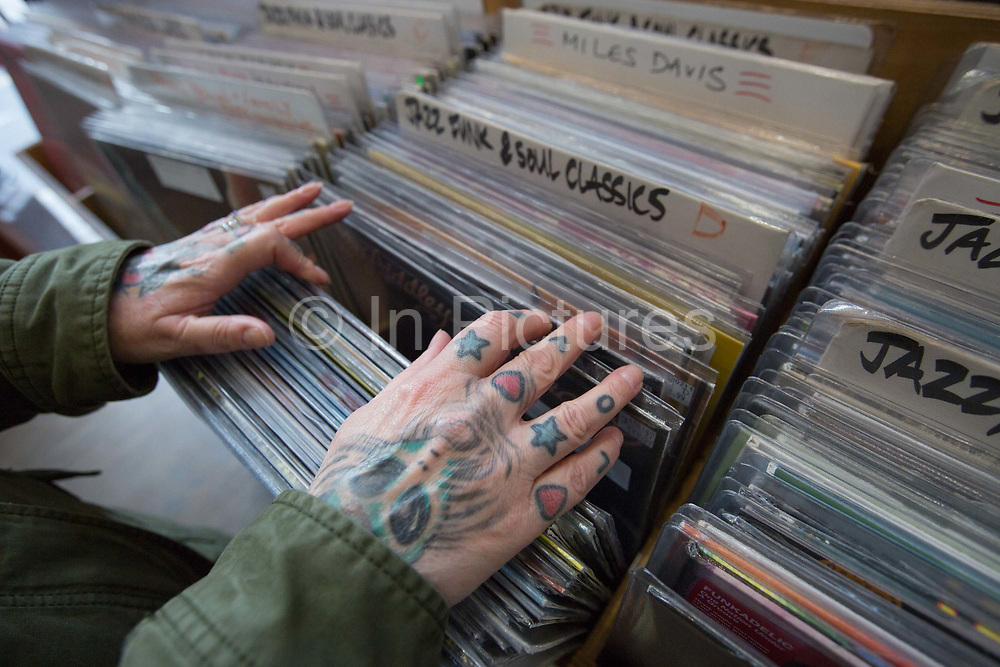A lady with tattoos on her hands spelling the word love, searches for vinyl in a Soho record shop on the 23rd March 2018 in Central London, United Kingdom.