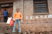 Girl in westernised clothing stands outside her house near Lugu Lake, Yunnan, China.