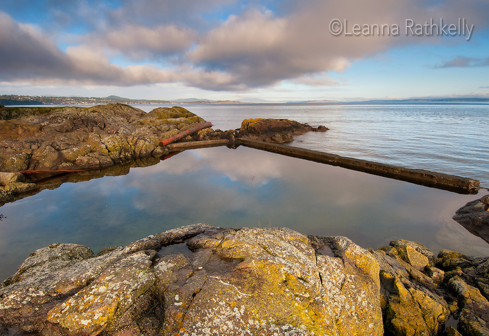 A winter sky is reflected in the water of a protected ocean pool off Margaret Bay, Saanich, Victoria, BC