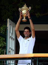 Novak Djokovic with the trophy on a centre court balcony after winning the Gentlemen's singles final on day thirteen of the Wimbledon Championships at the All England Lawn Tennis and Croquet Club, Wimbledon.