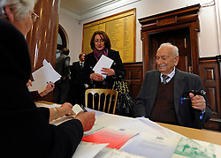 """© Licensed to London News Pictures. 02/02/2012, Kingston Upon Thames, UK. 104 year-old becomes Britain's oldest new citizen. Officials check Mr Khanjar's paperwork is in order. 104 year-old TAUFEEK KHANJAR became a British Citizen at a ceremony held by Surrey County Council today (01 February 2012). Mr Khanjar is originally from Iraq and worked as a jewellery maker in Baghdad. He came to the UK six years ago to live with his daughter Nada Dabis, 59, in South Cheam, Surrey, where he enjoys walking, feeding the birds, playing cards and listening to music. He is a widower with four sons and two daughters. Durning the ceremony Mr Khanjar took an oath to the Queen, pledging that he will be a faithful citizen and obey the laws of the country. He explained the secret to a long and healthy life was to """"never get stressed and be relaxed"""".  Photo credit : Stephen Simpson/LNP"""