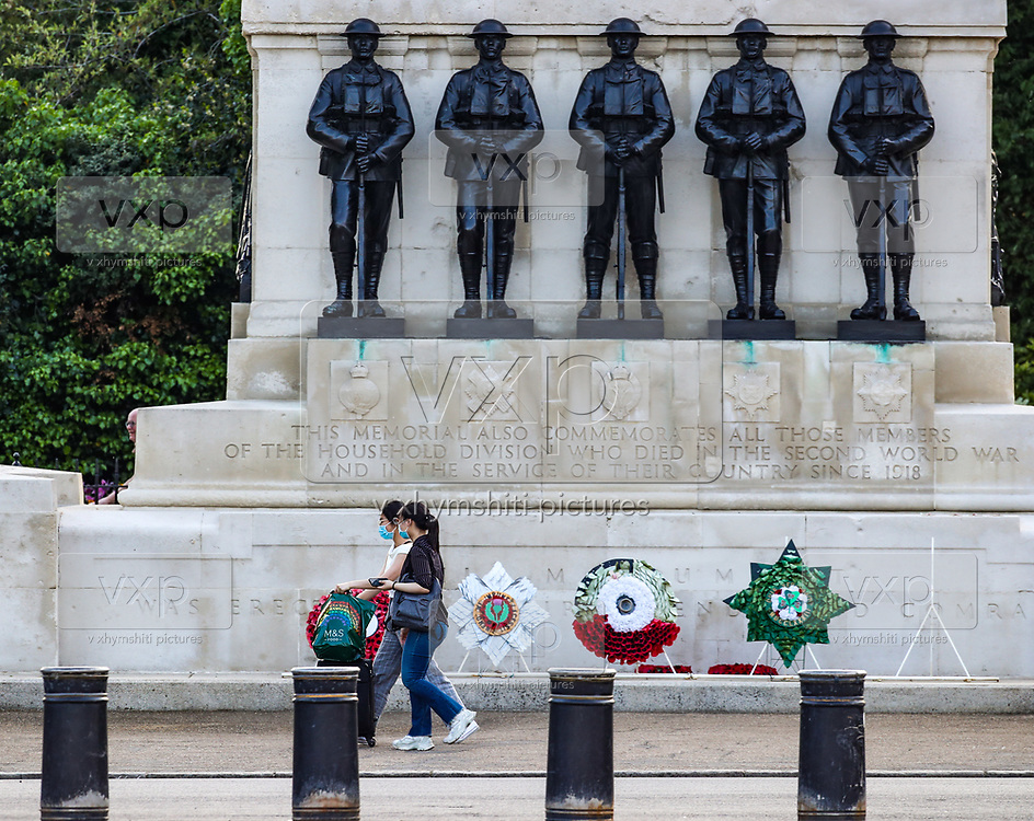 People wearing protective face mask walks in front of a memorial in London, Friday, May 8, 2020 on the 75th anniversary of the end of World War II in Europe. The 75th anniversary of the end of World War II in Europe should be all about parades, remembrances, and one last great hurrah for veteran soldiers who are mostly in their nineties. Instead, it is a time of coronavirus lockdown and loneliness spent in search of memories both bitter and sweet. (Photo/ Vudi Xhymshiti)