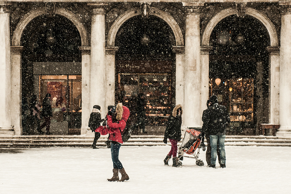 """VENICE, ITALY - 28th FEBRUARY/01st MARCH 2018<br /> Tourists enjoy the atmosphere created by a snowfall in Saint Mark square in Venice, Italy. A blast of freezing weather called the """"Beast from the East"""" has gripped most of Europe in the middle of winter of 2018, and in Venice A snowfall has covered the city with white, making it fascinating and poetic for citizen and tourists.   © Simone Padovani / Awakening"""
