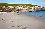 Woman walking on sandy beach at Bagh a Deas, South Bay, Vatersay island, Barra, Outer Hebrides, Scotland, UK