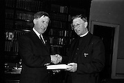 """21/5/1965<br /> 5/21/1965<br /> 21/5/1965<br /> <br /> President de Valera recived an inscribed mathematic textbook """"Matamatic na h'ard Teistimeireachta"""" from the author An Br. Tomás Ó Catnain, Mount Sion Waterford.<br /> <br /> Mr. Kevin Boland T.D and An Br. Tomás Ó Catnain shaking hands at the event."""